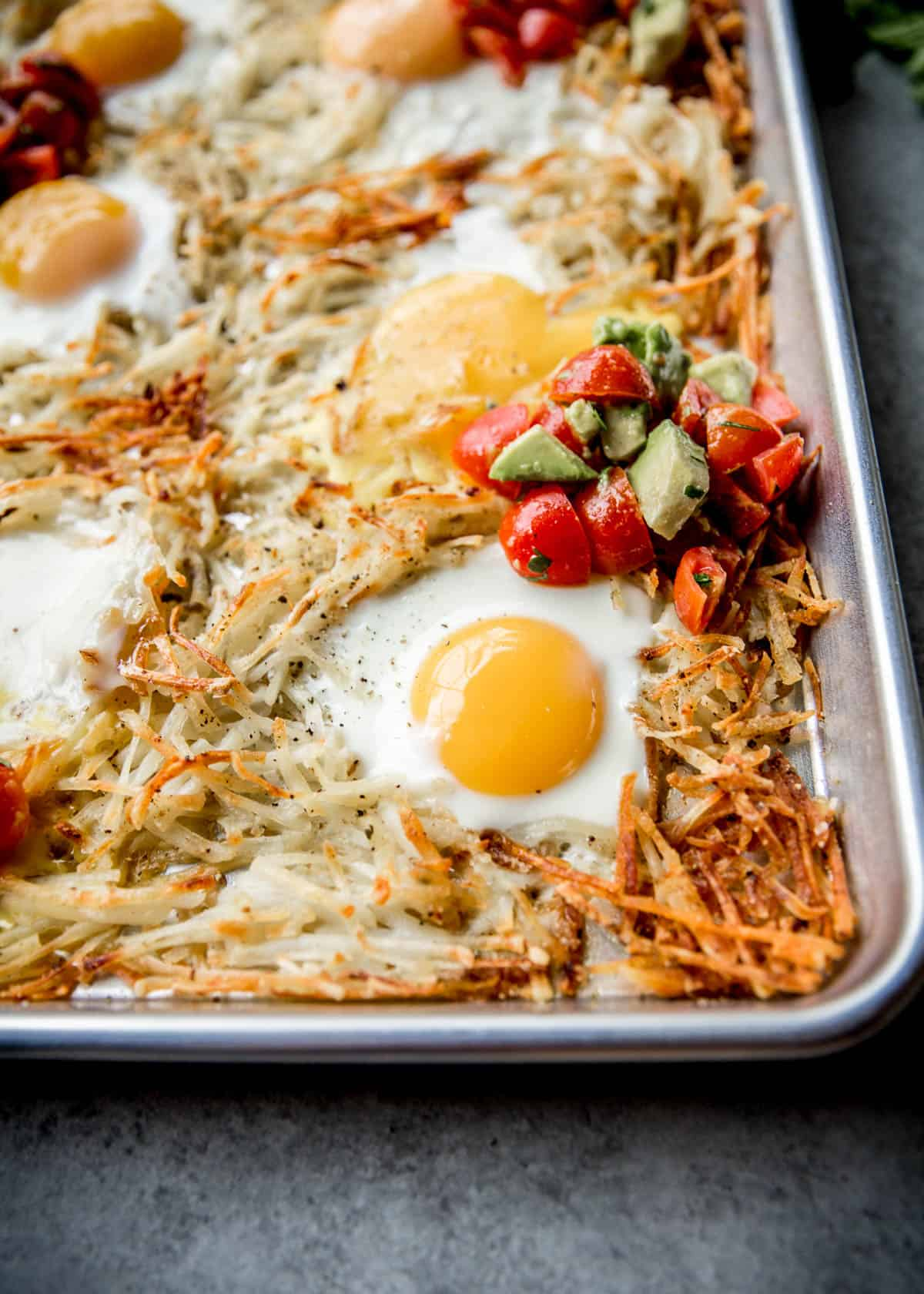 hash browns and a fried egg on a sheet pan