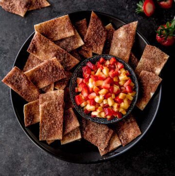 baked cinnamon chips and a bowl of fruit salsa on a black tray