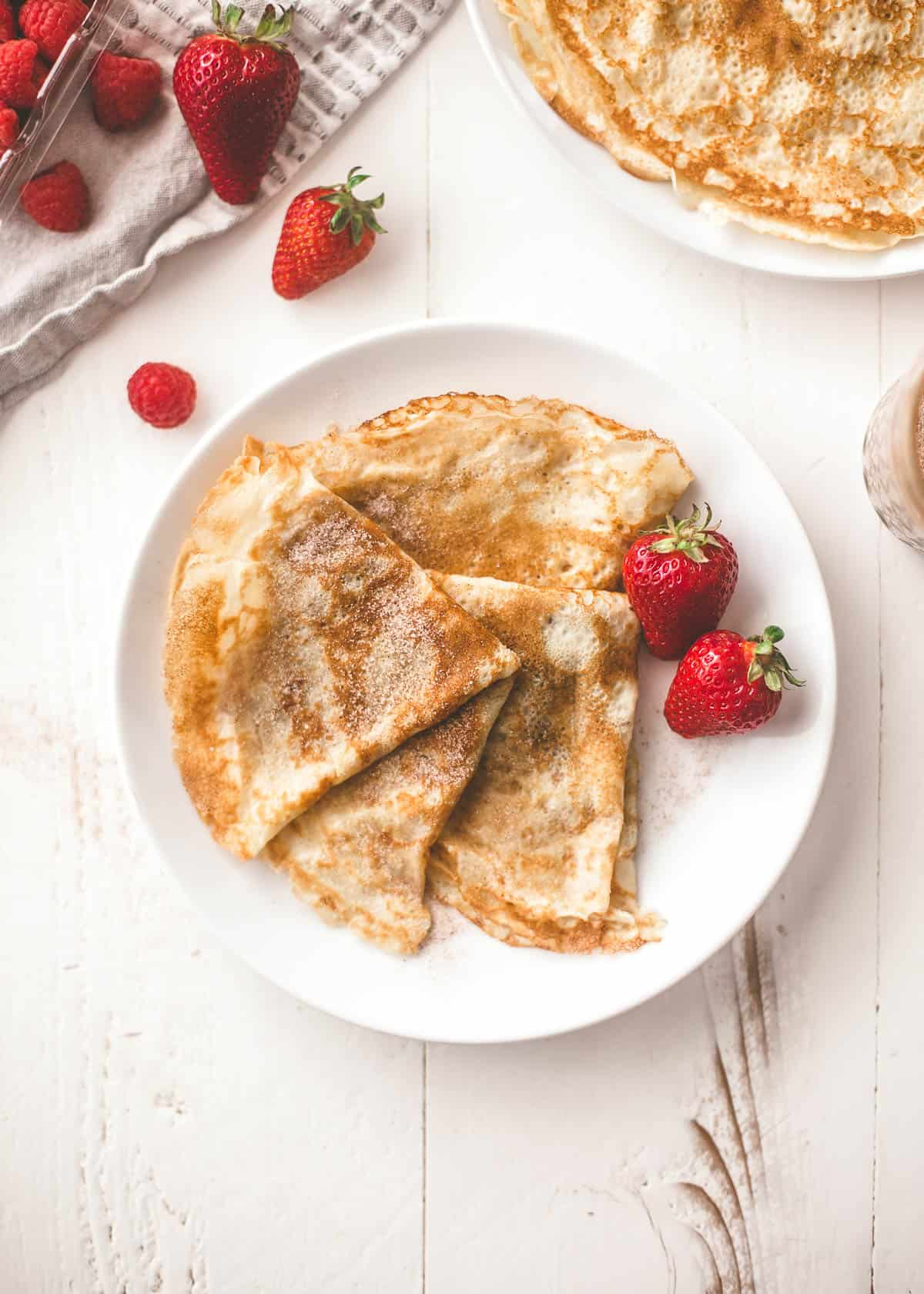 crepes and berries on a white plate