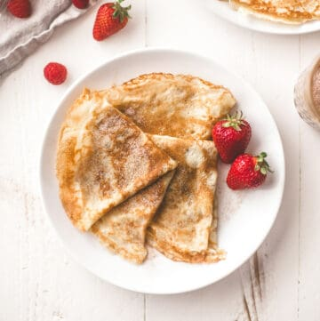 crepe and berries on a white plate