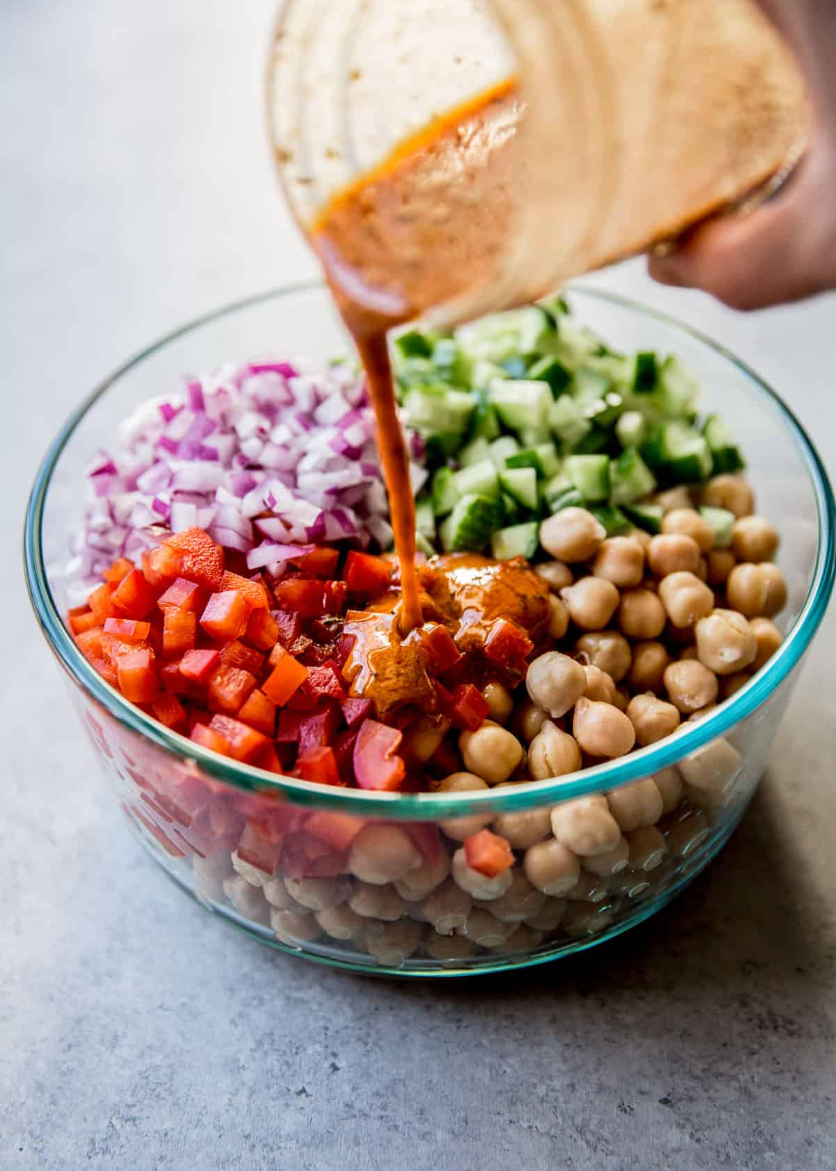 adding dressing to chickpeas and vegetables in a clear glass bowl