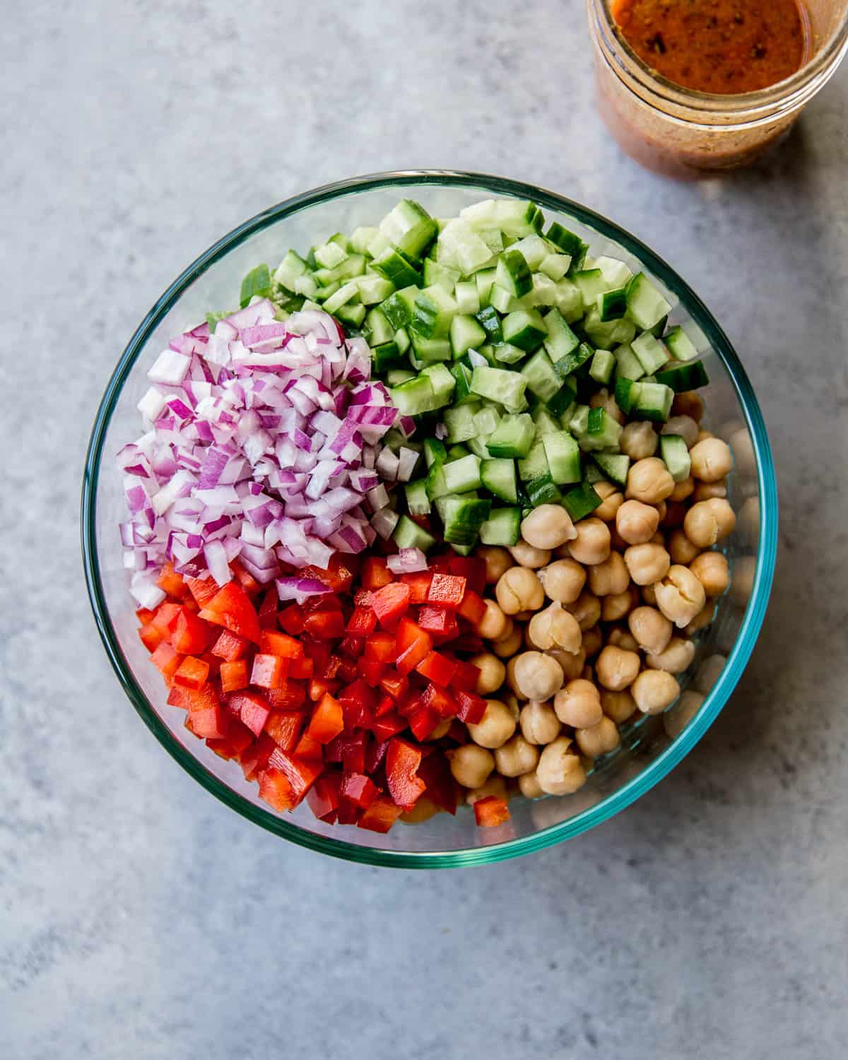 chickpeas, bell peppers, cucumbers and onions in a clear glass bowl