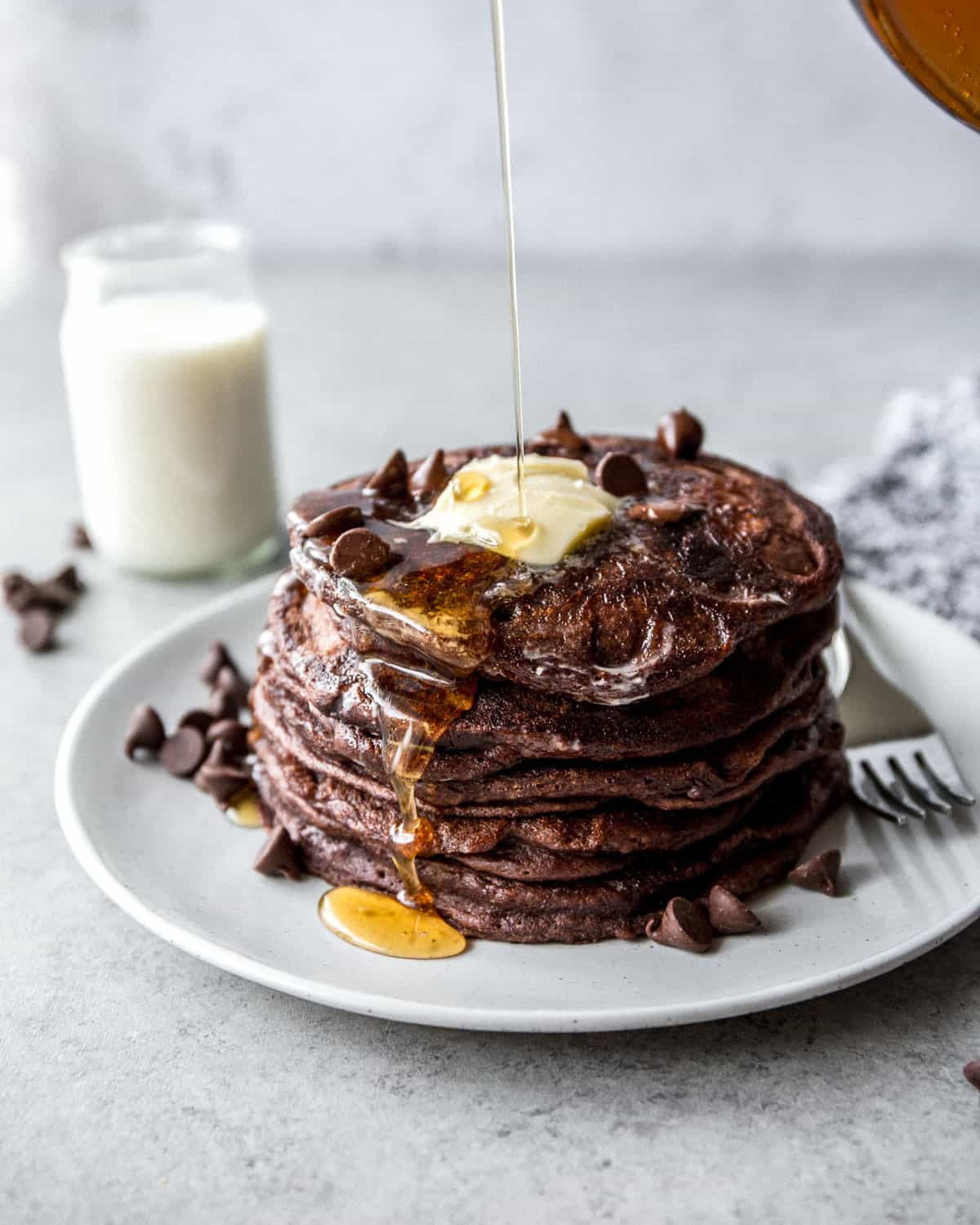 a stack of chocolate pancakes on a white plate