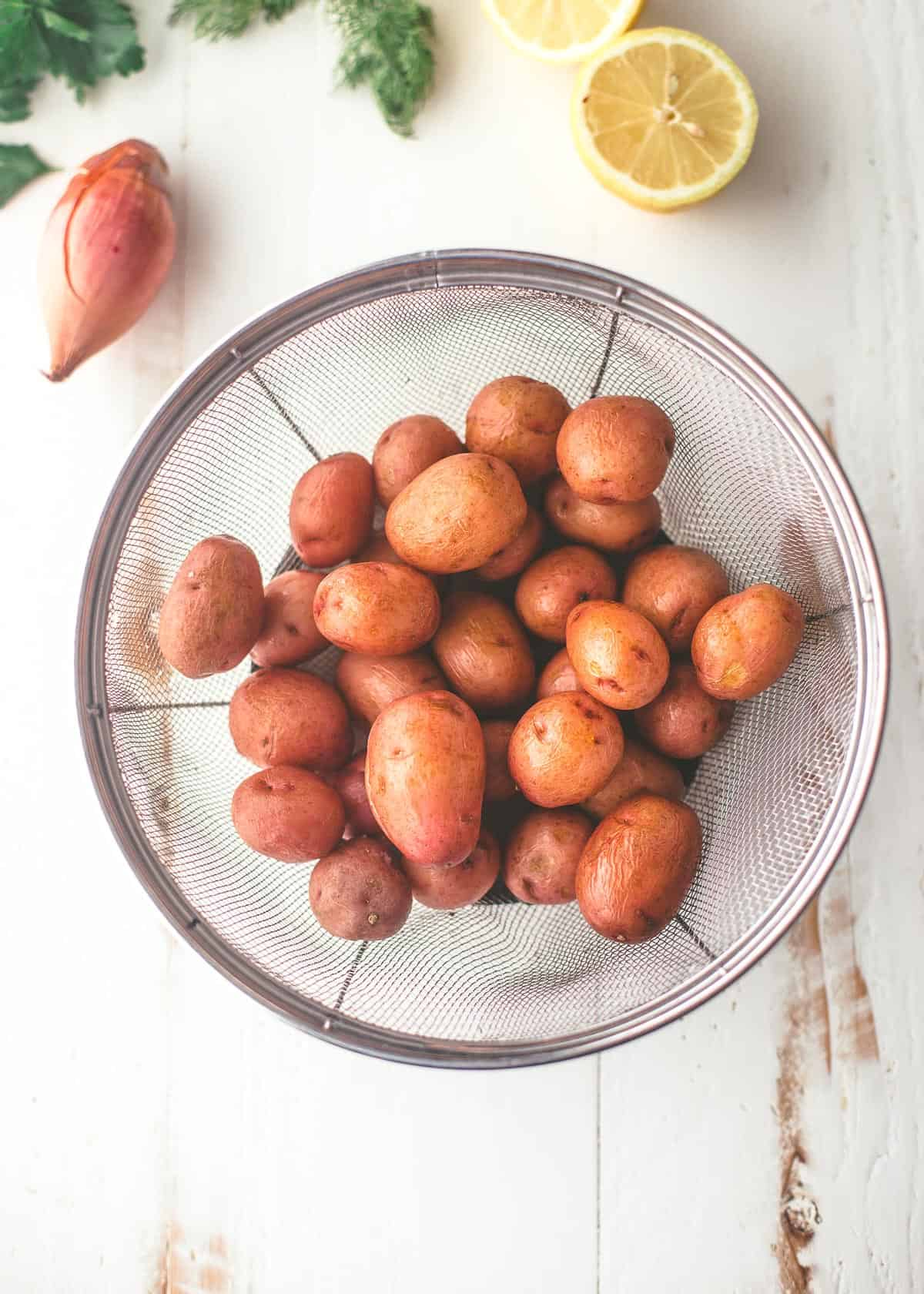 potatoes in a colander on a white table