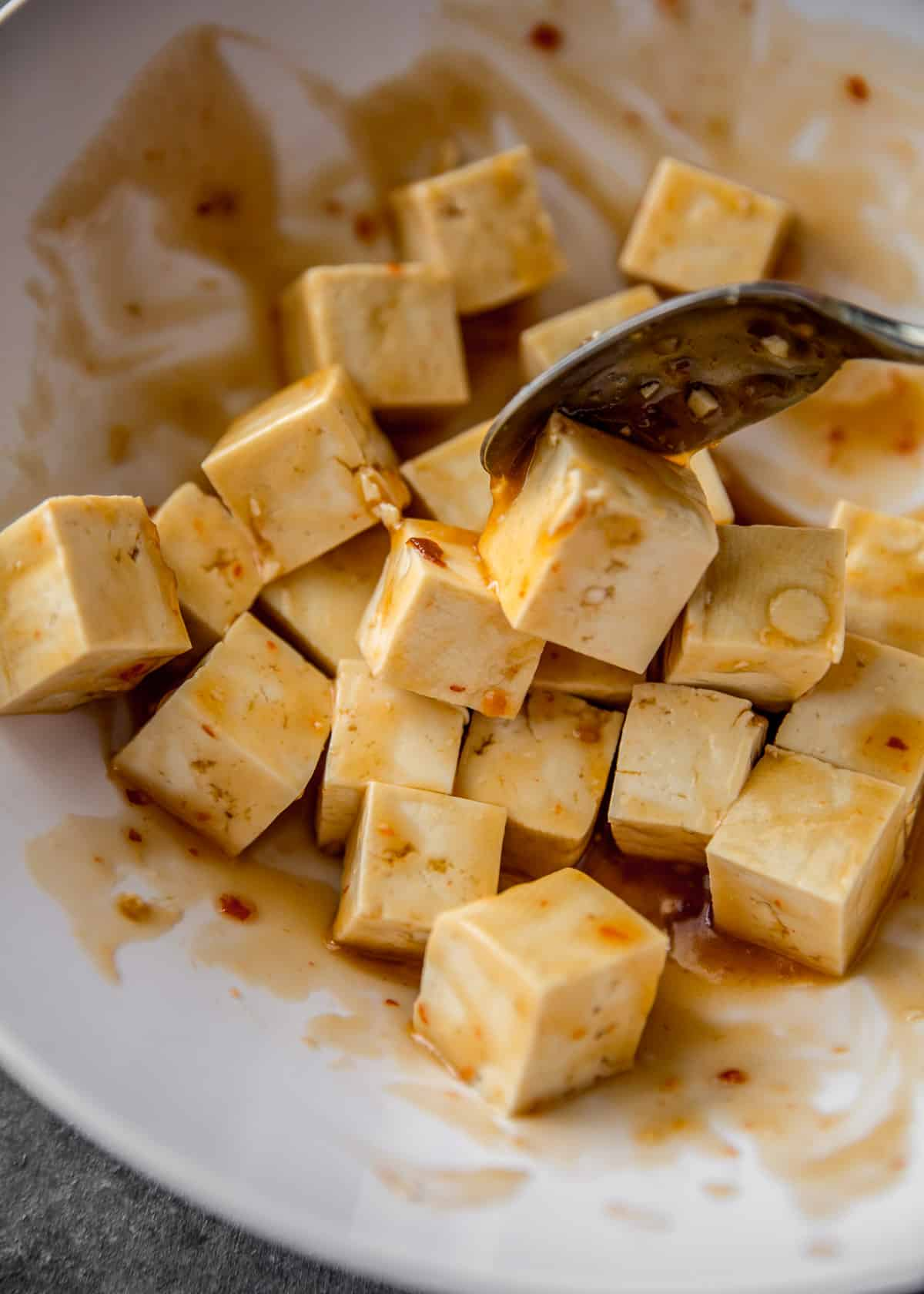 tossing tofu with marinade