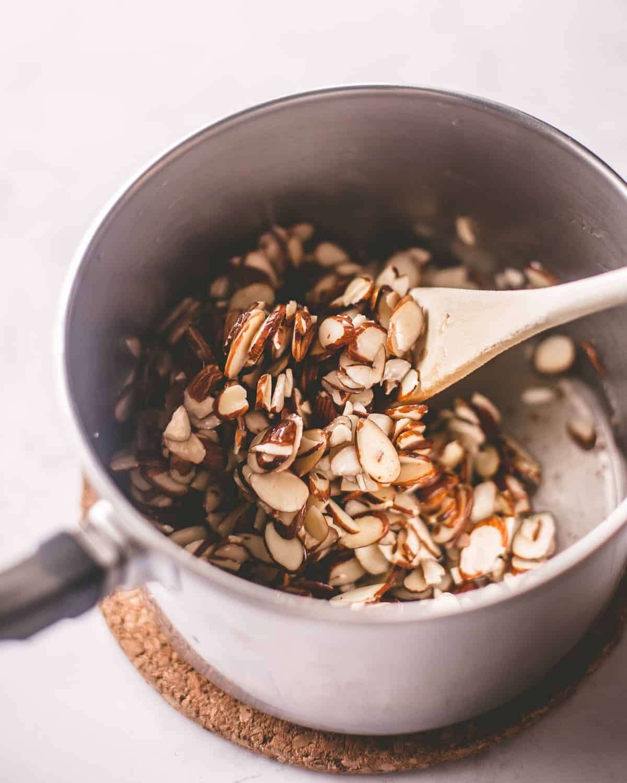 stirring almonds in a saucepan