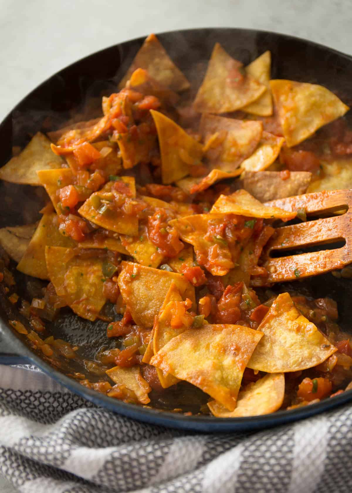 stirring baked tortilla chips into tomatoes in a cast iron skillet