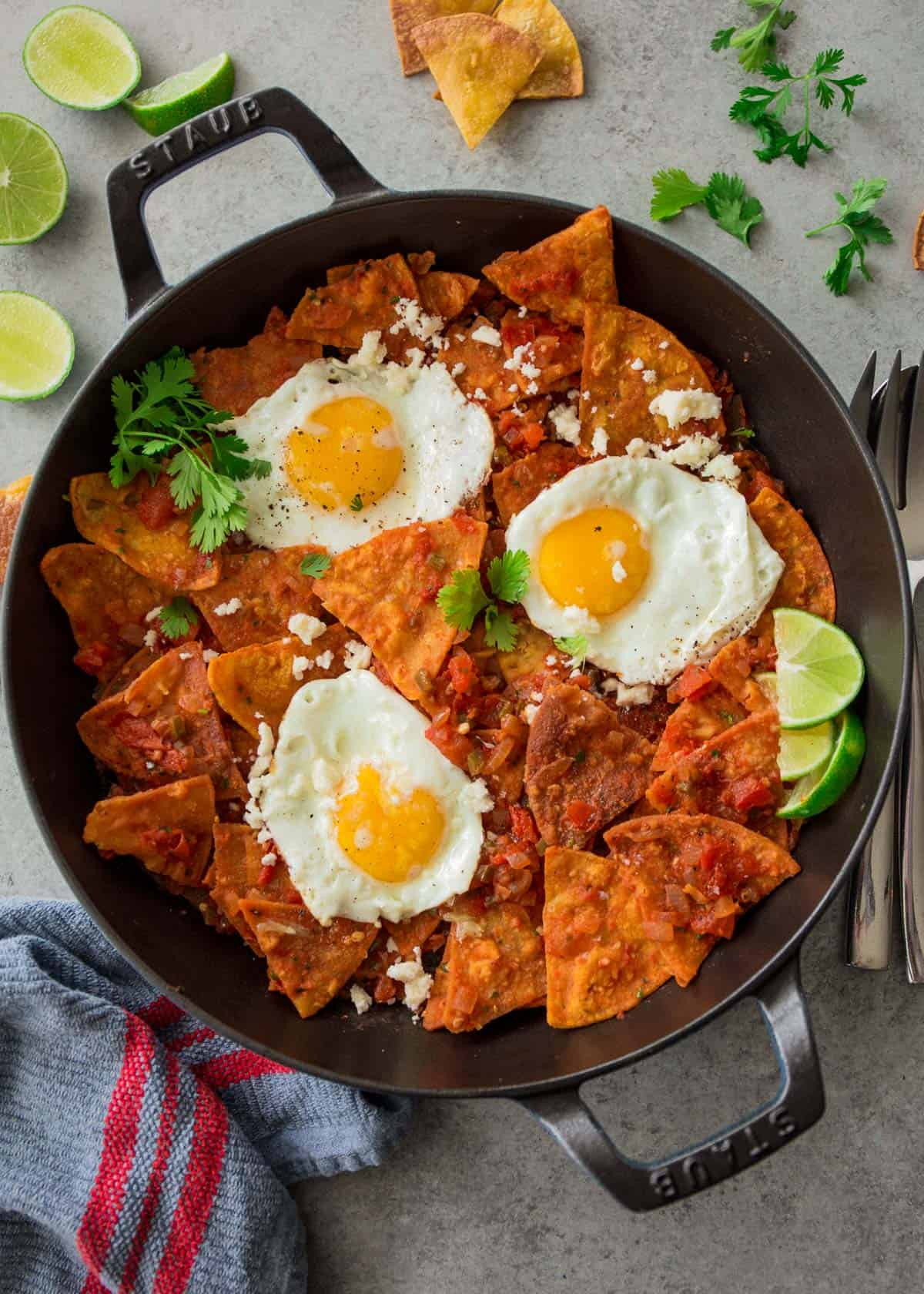 chips, tomatoes and fried eggs in a cast iron skillet