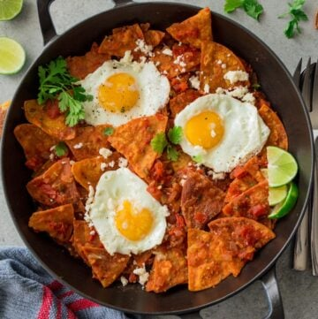 tomatoes, fried eggs and tortilla chips in a cast iron skillet