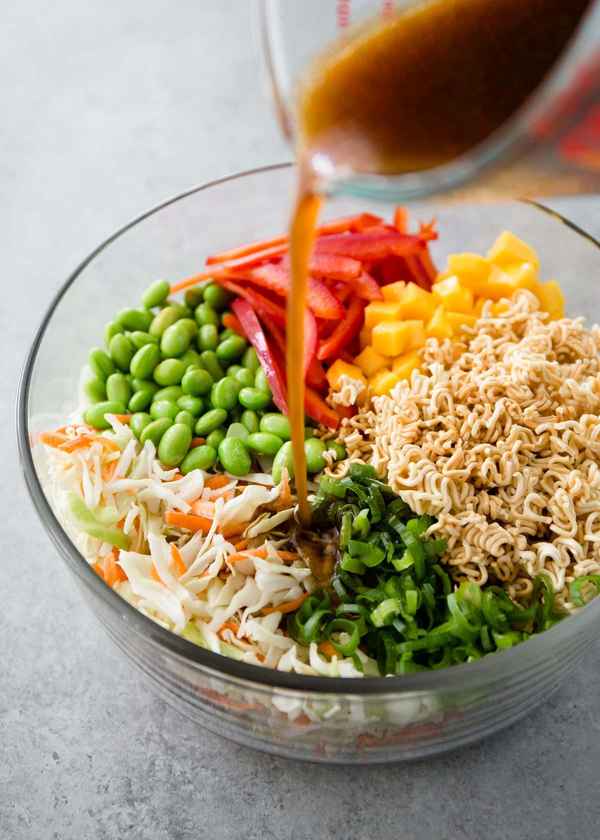 dressing being poured over crunchy ramen noodle salad
