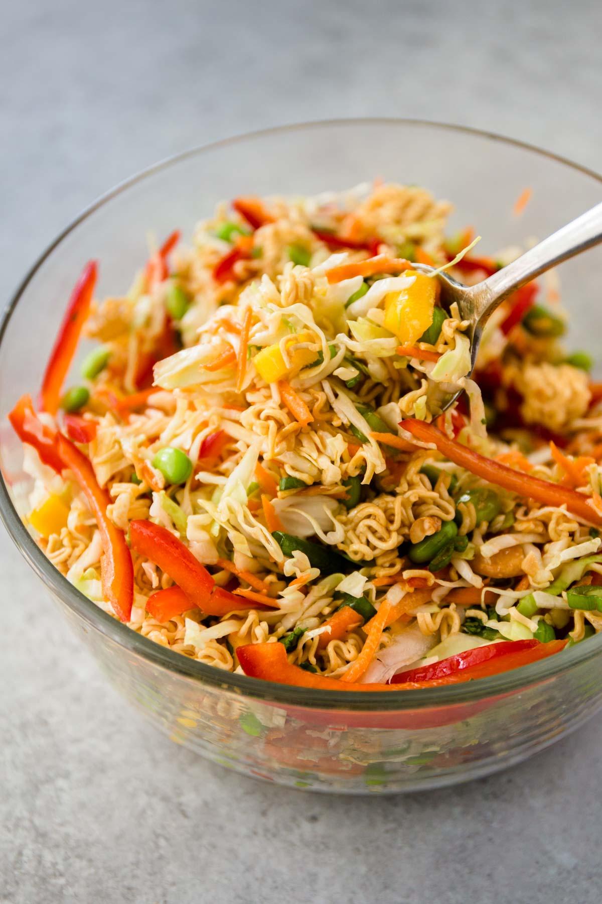 a spoon in a clear bowl of crunchy ramen salad