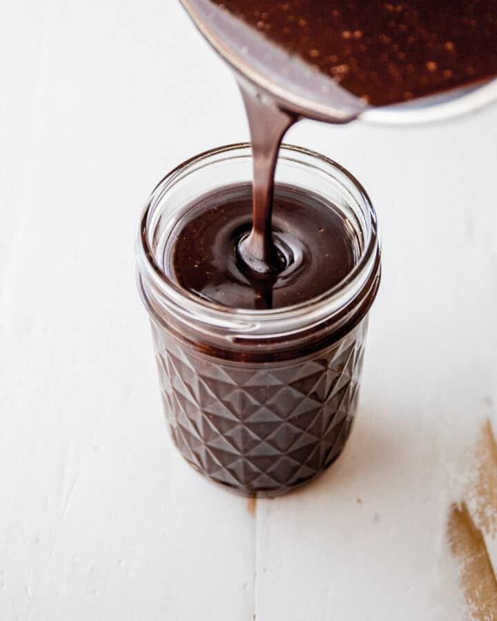 pouring fudge sauce into a small glass jar