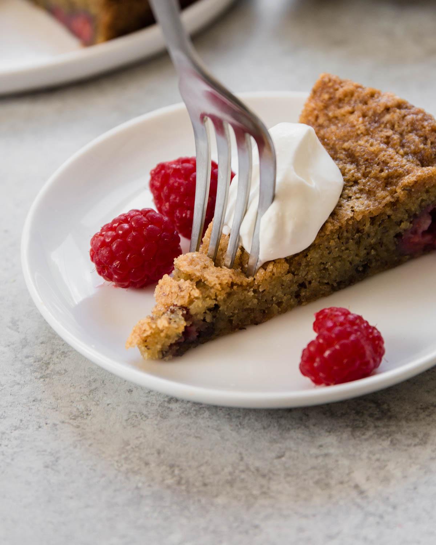 fork cutting into slice of raspberry almond snack cake