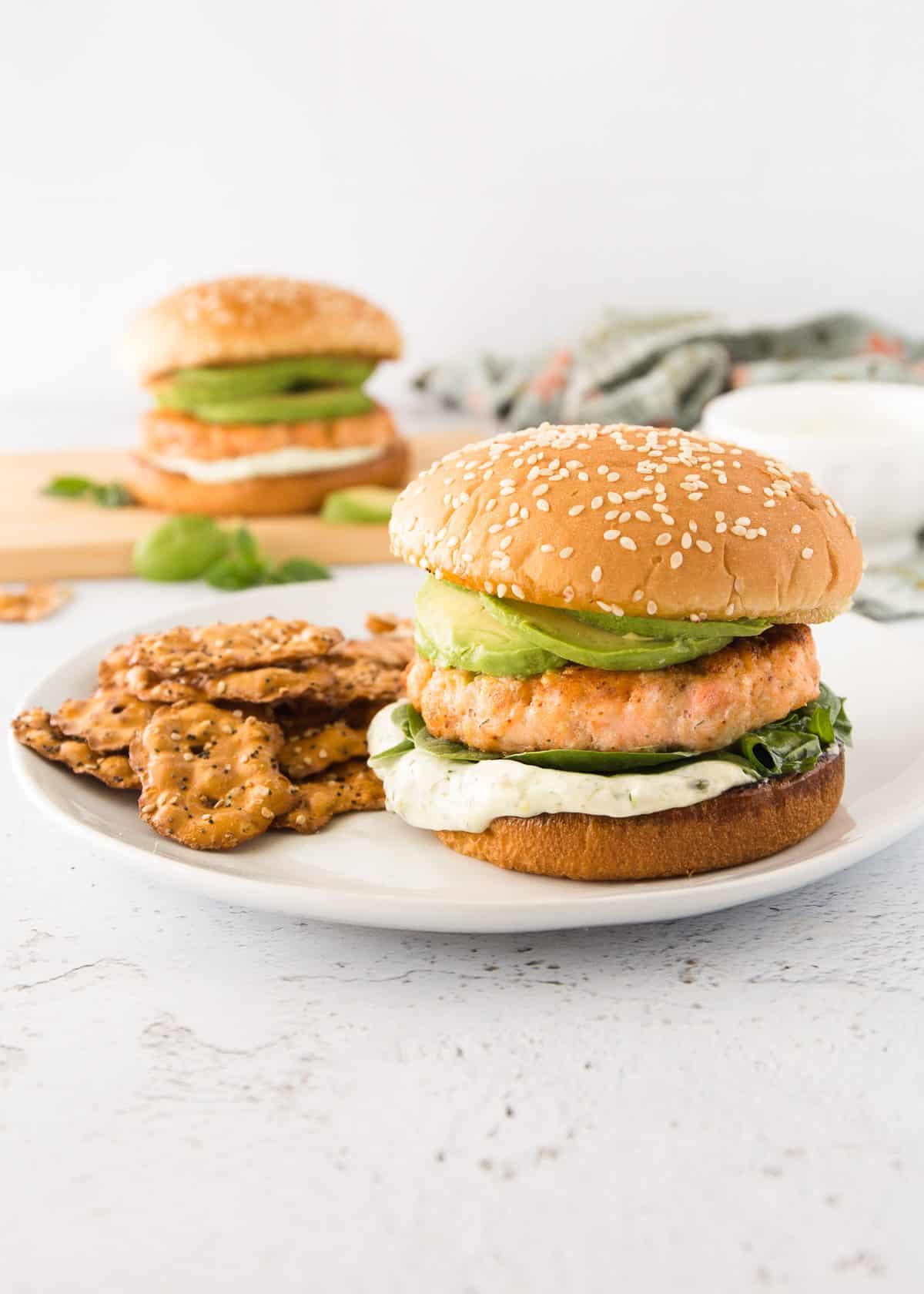 a salmon burger on a bun on a white plate