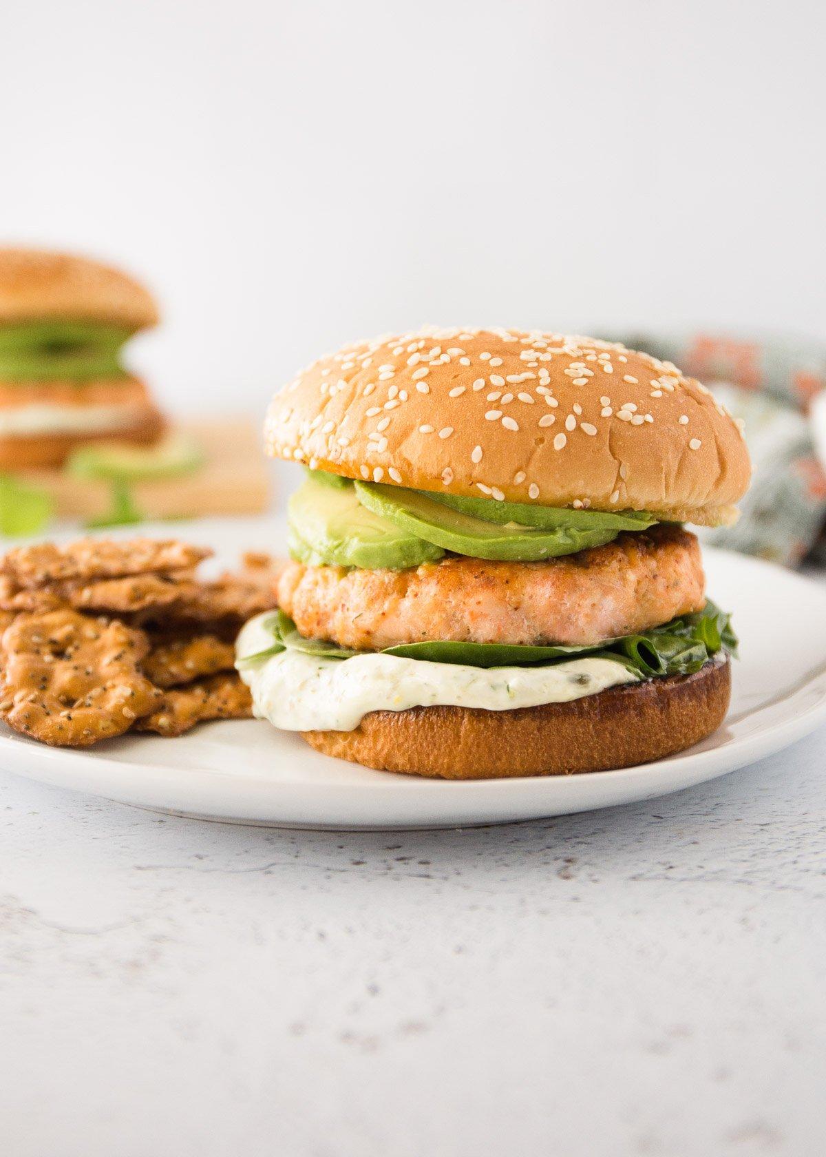 salmon burger on a bun on a white plate