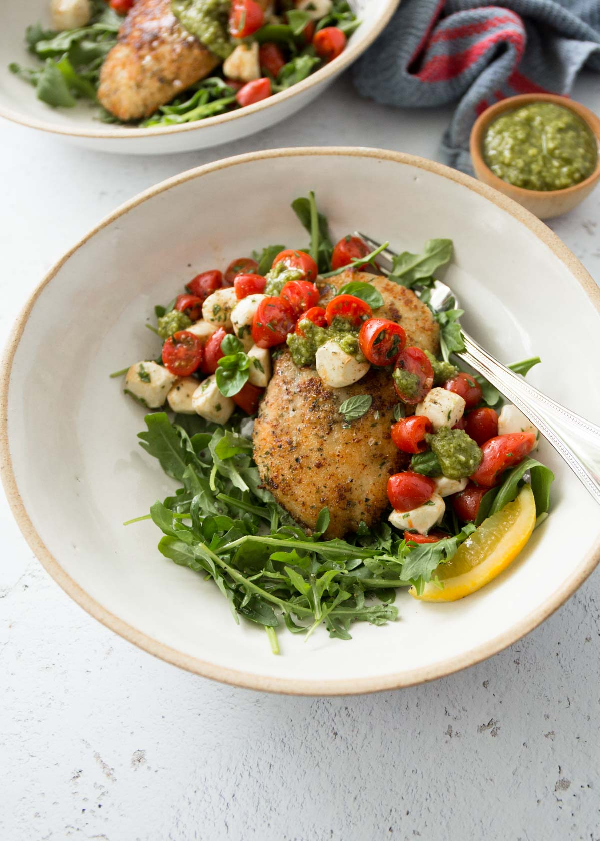crispy chicken with balsamic tomato salad in a white bowl