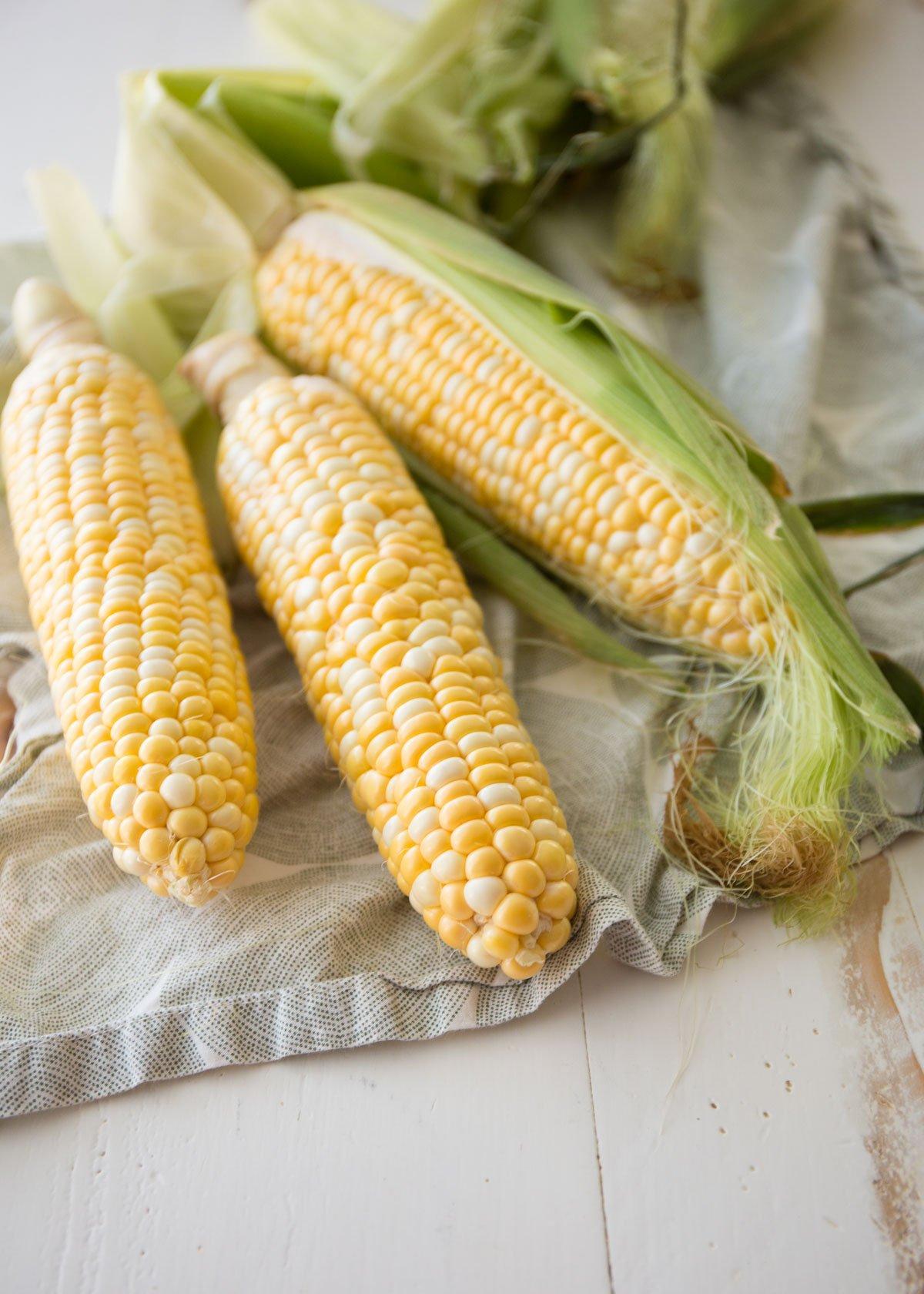 3 cobs of corn on a tan towel