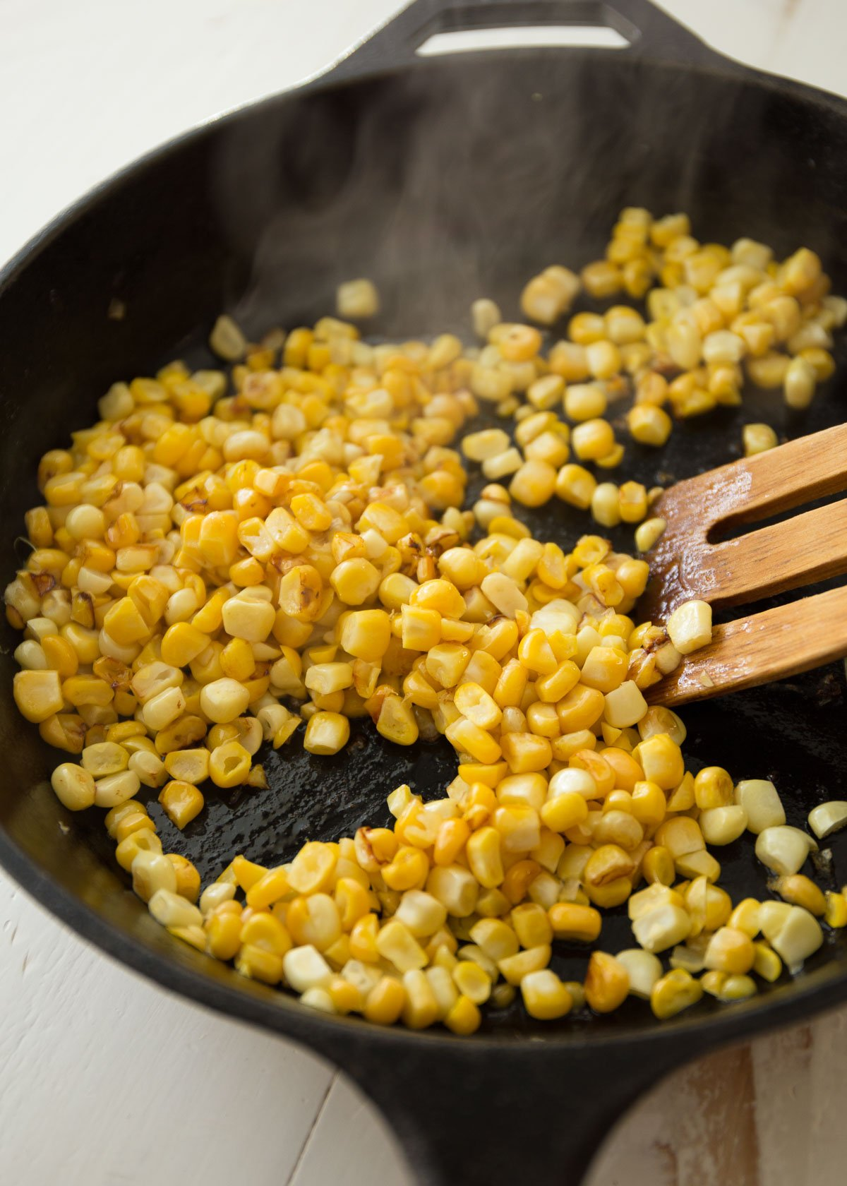 sauteeing corn kernels in a cast iron skillet