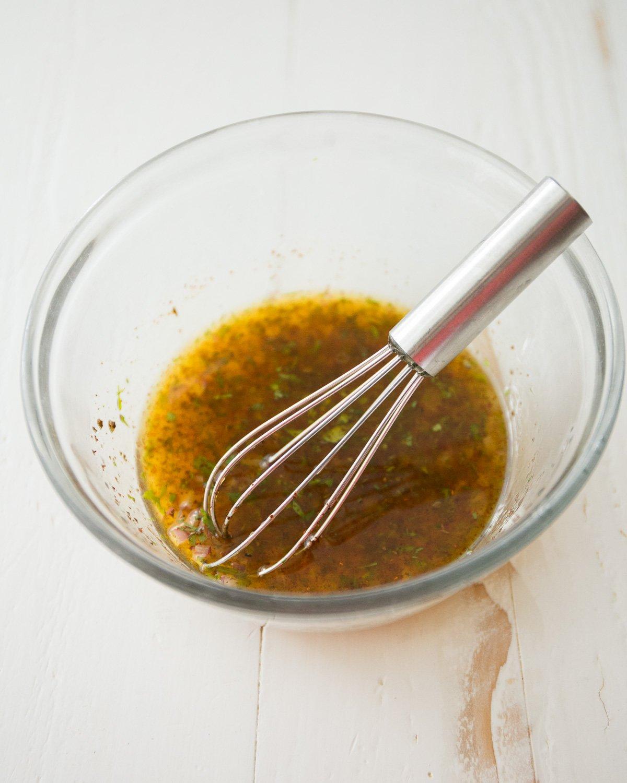 stirring vinaigrette in a clear glass bowl