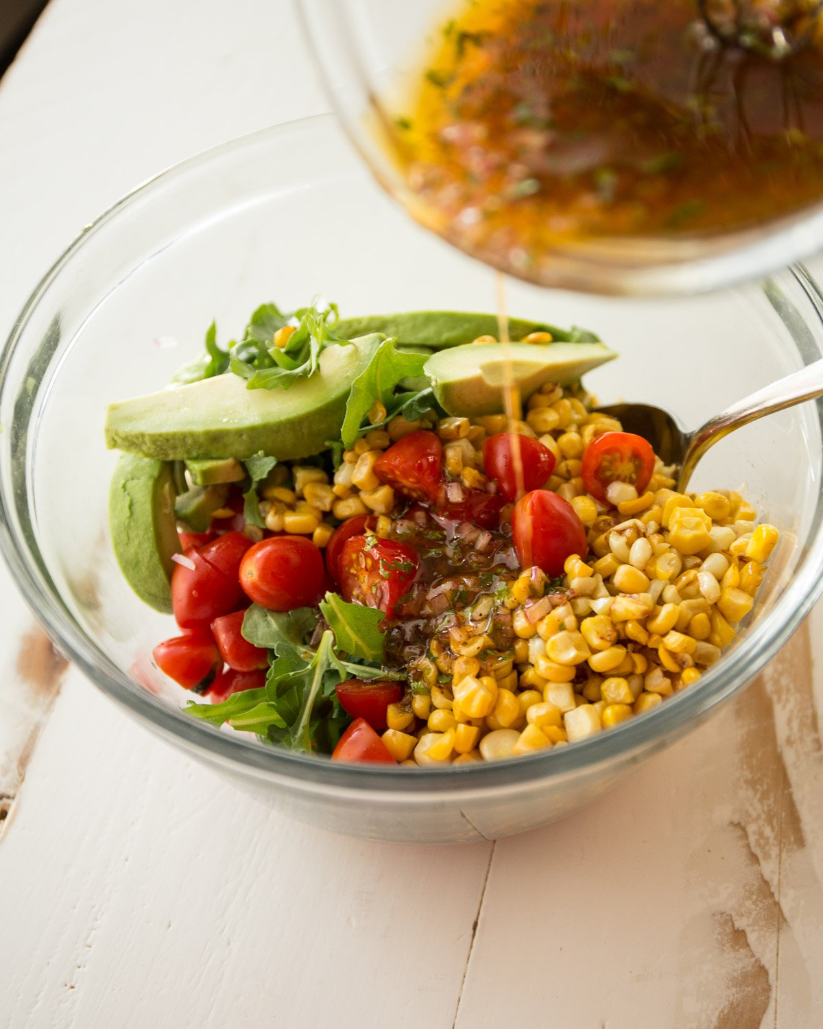 mixing corn, tomato and avocado salad in a clear glass bowl