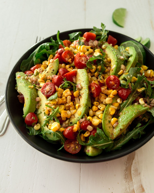 corn, tomato and avocado salad in a black bowl