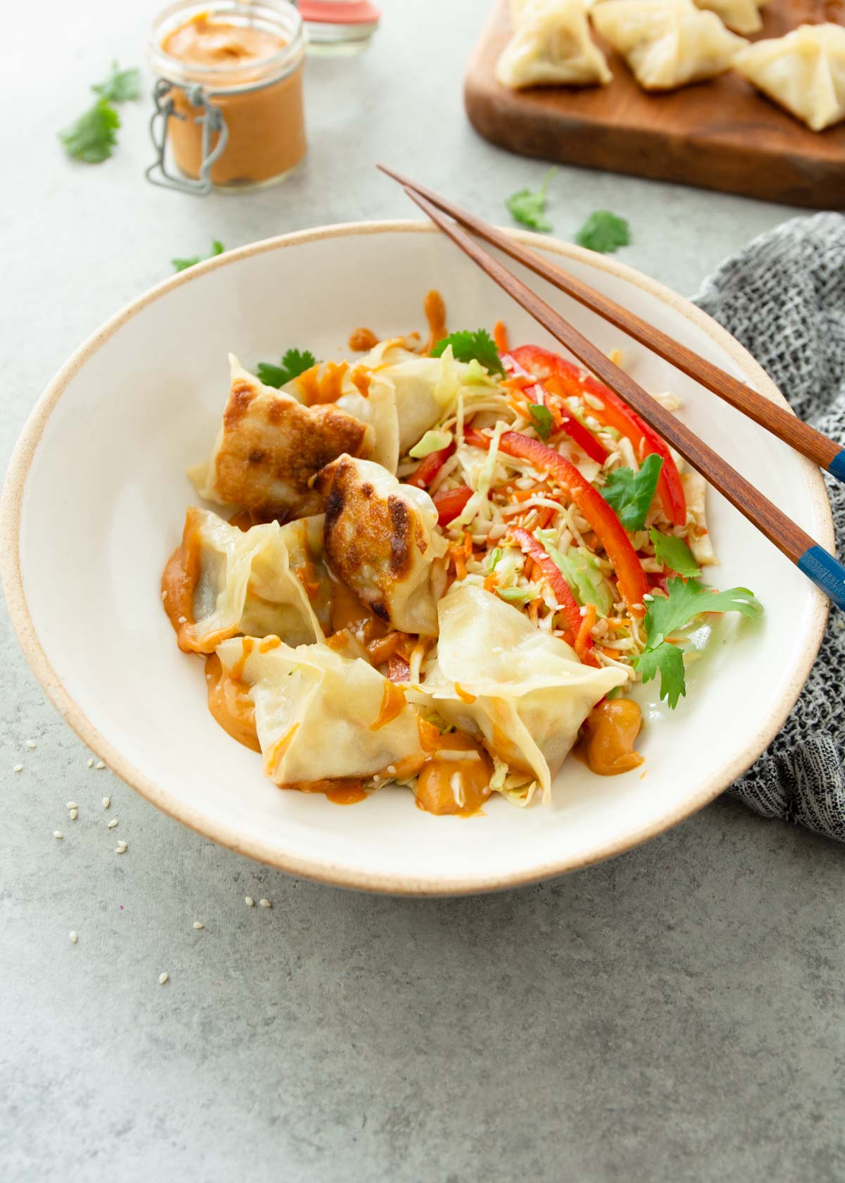 potstickers in a white bowl with chop sticks