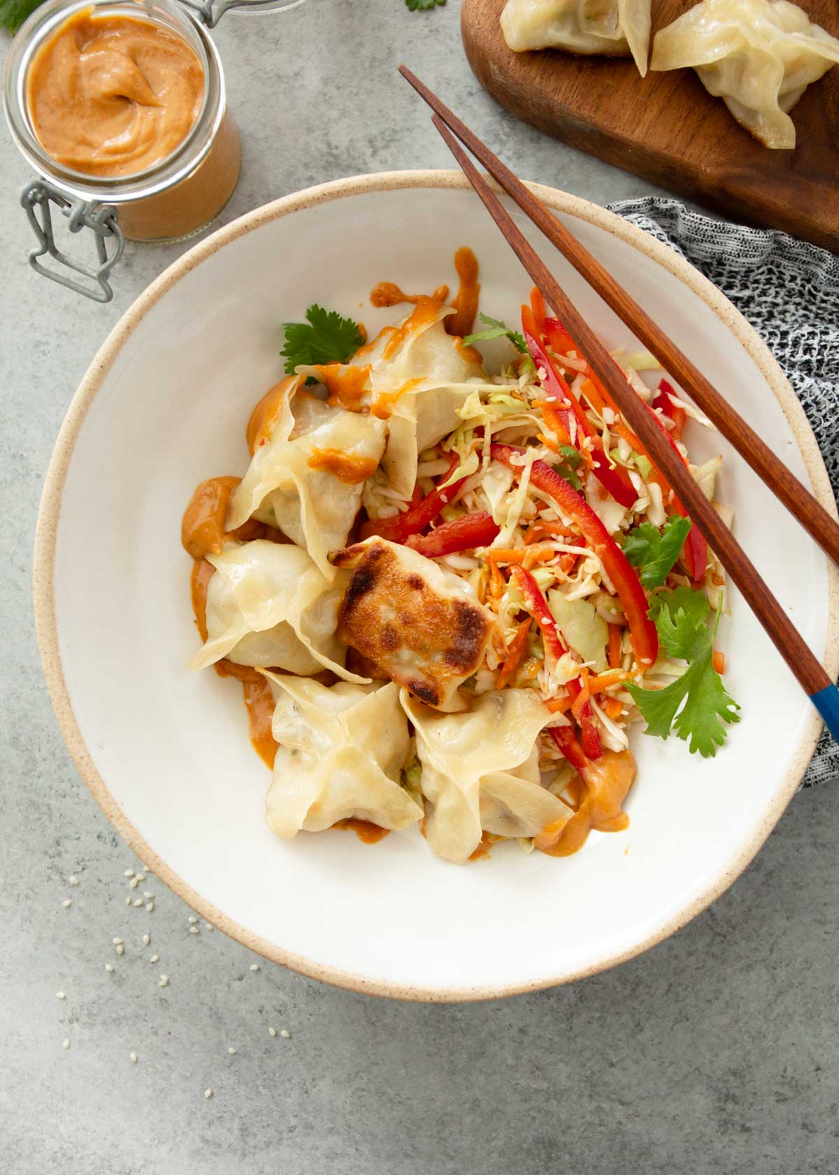 a white bowl with potstickers and slaw