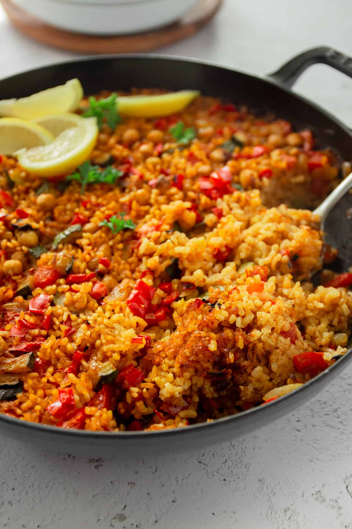 a spoon in a pan of vegetable paella