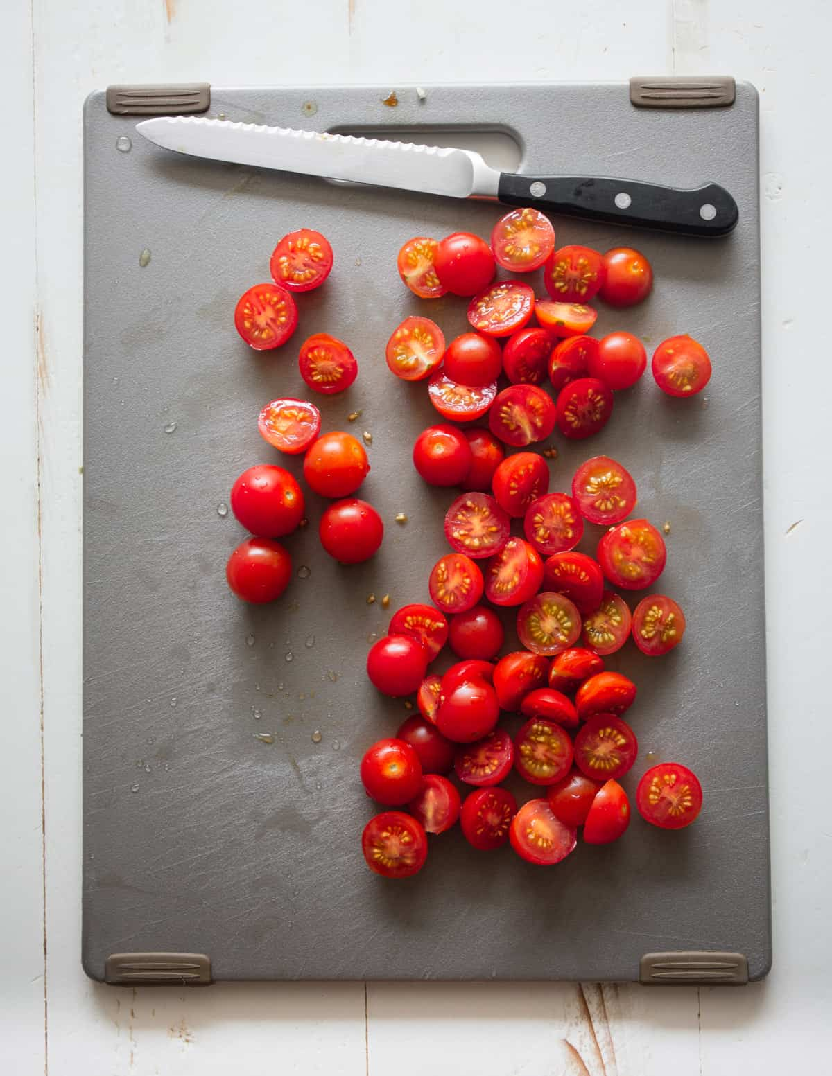 cutting tomatoes on a grey cutting board