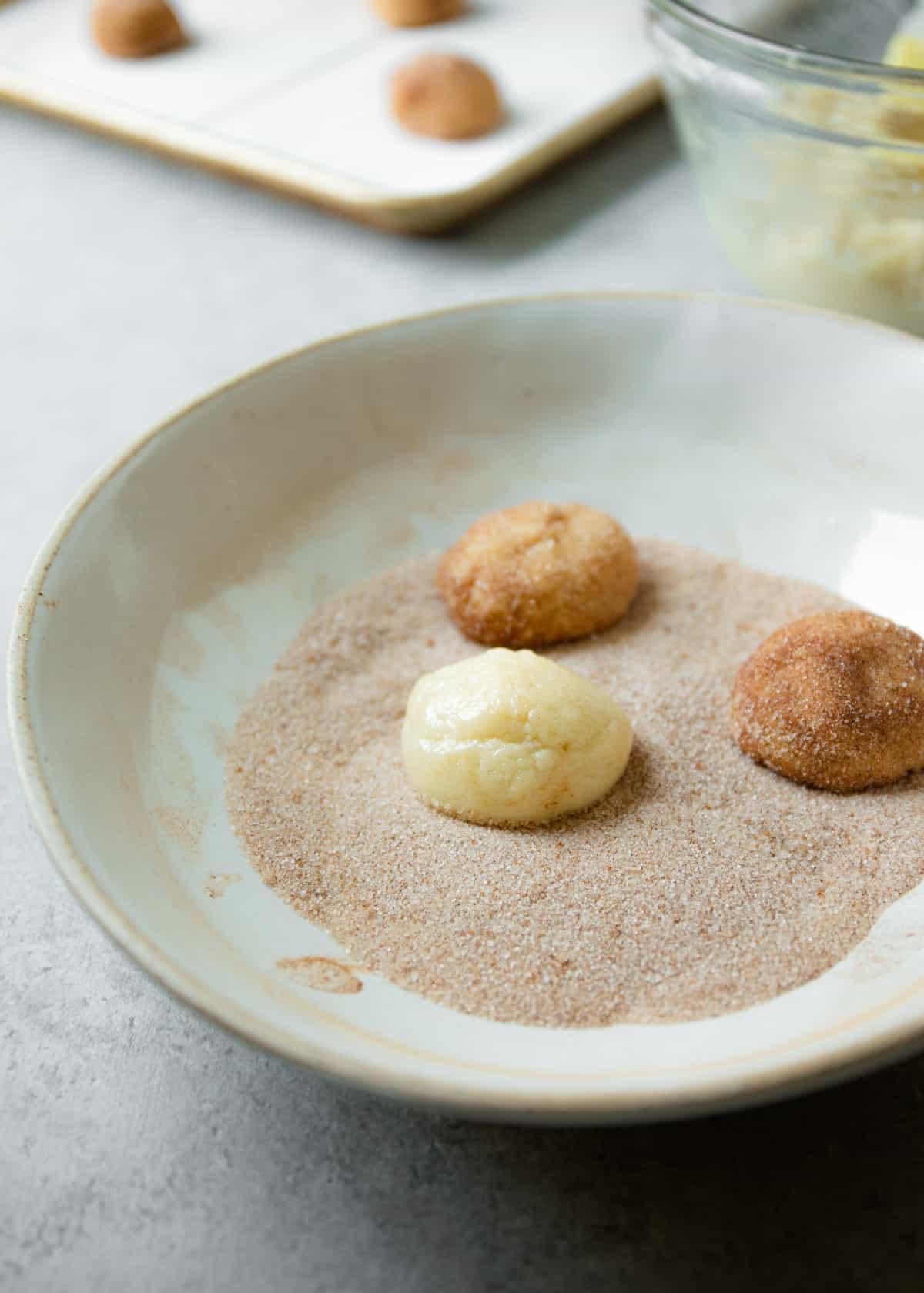 rolling cookie batter in cinnamon sugar