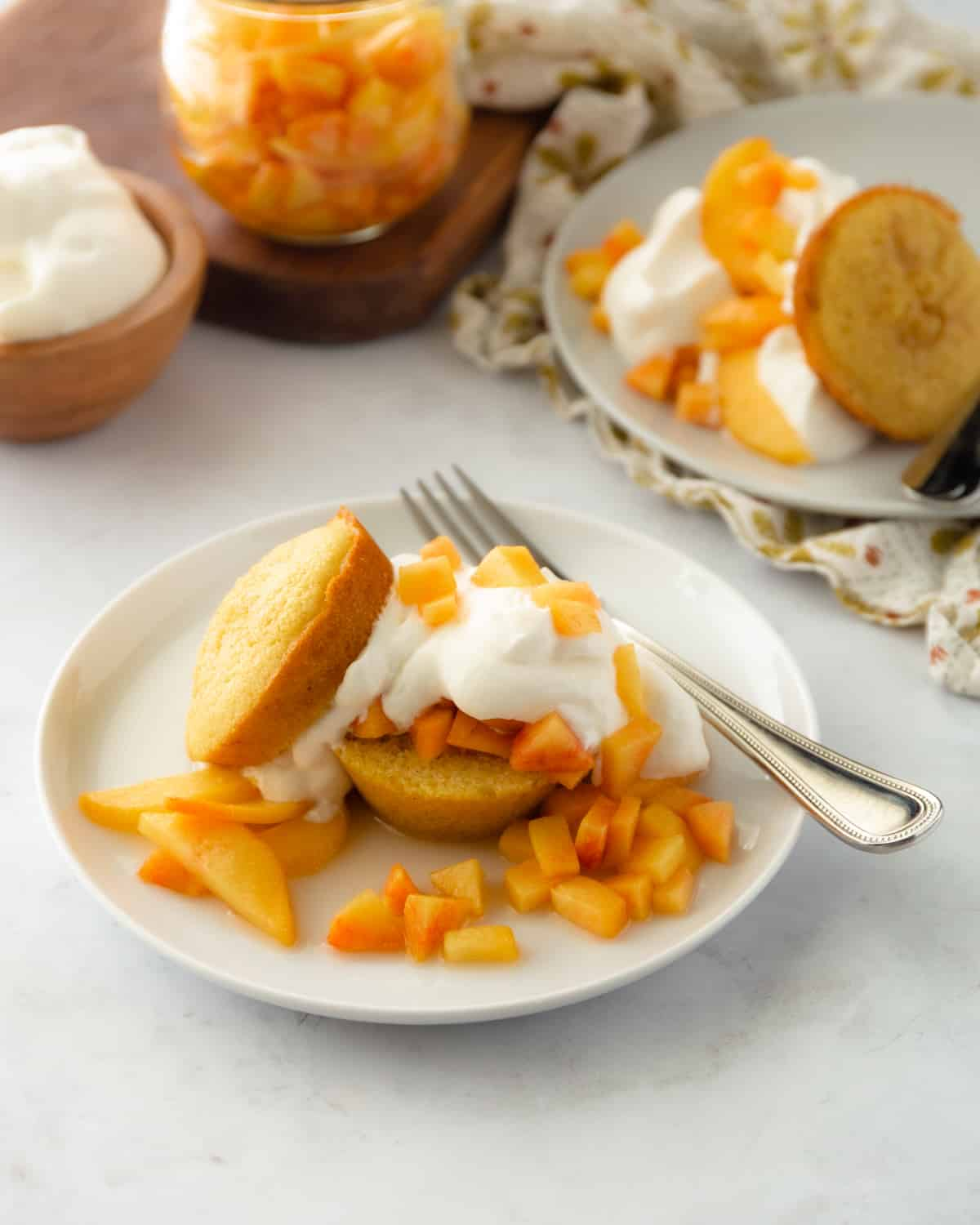 shortcakes and peaches on a white plate