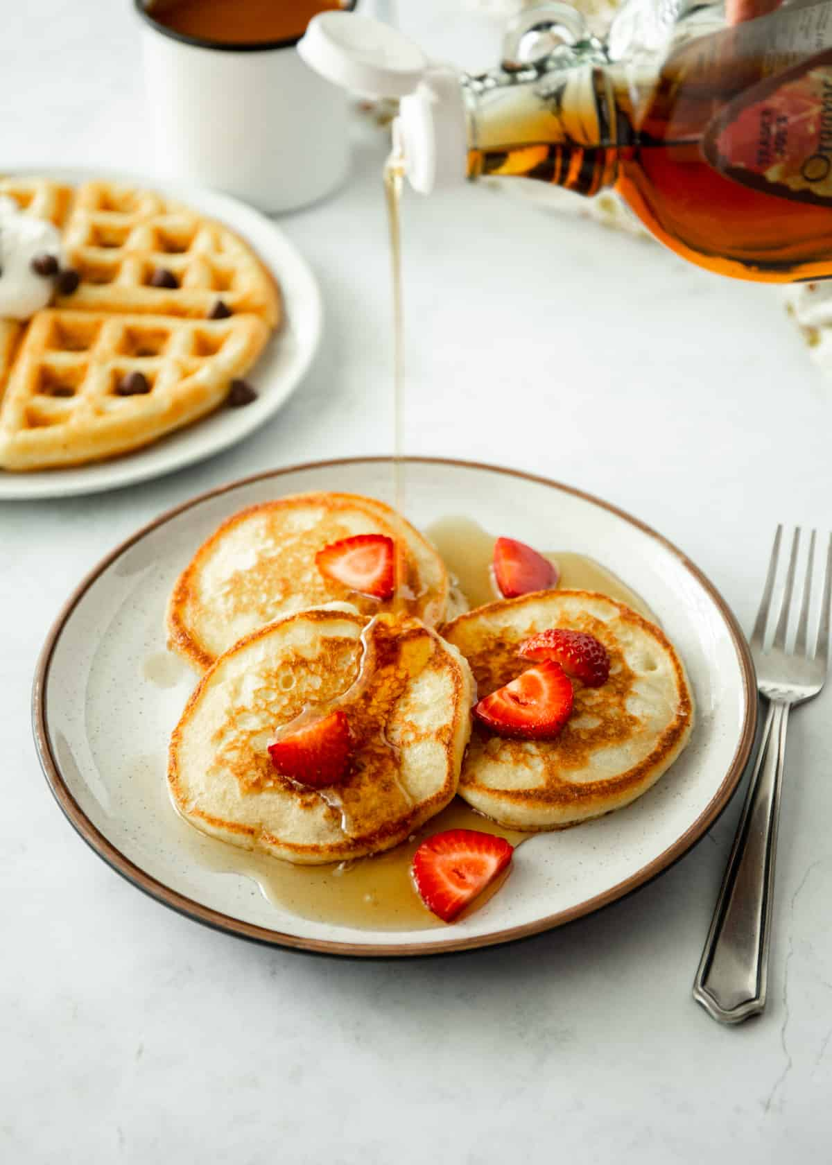 pouring syrup over pancakes with strawberries