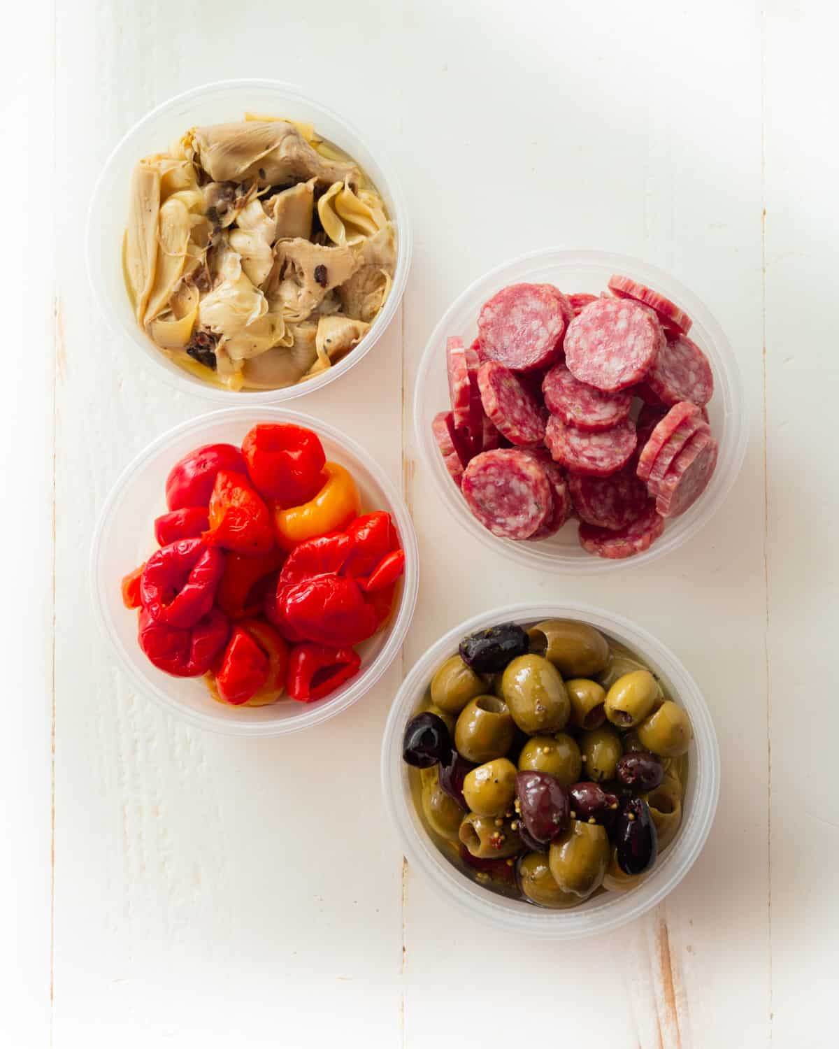 peppers, tortellini, sausage and olives in white bowls