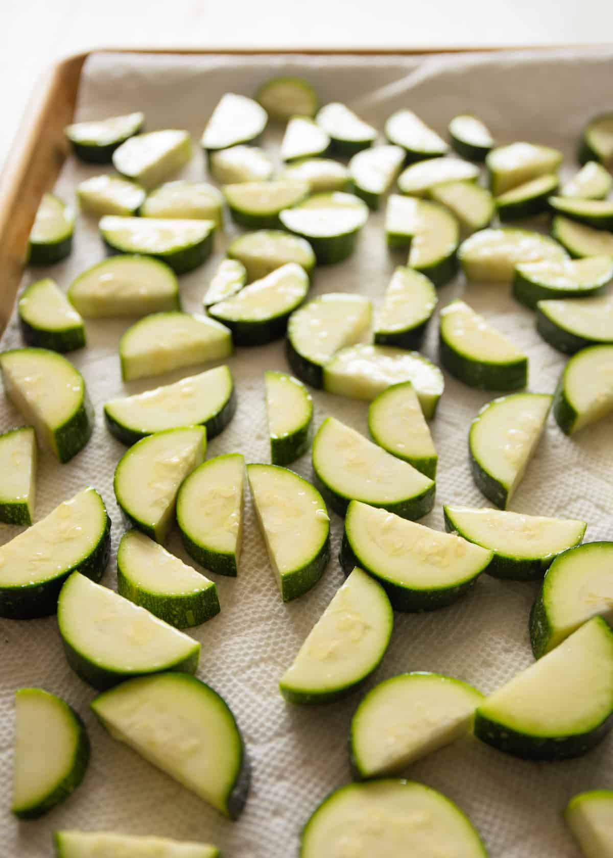 raw zucchini slices on a sheet pan