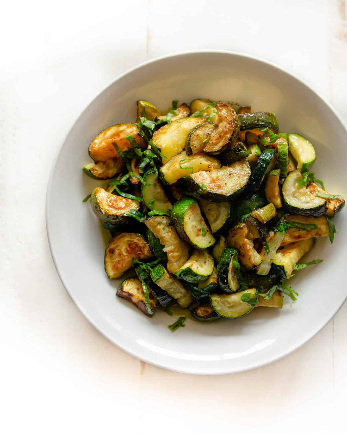 a white bowl of cooked zucchini