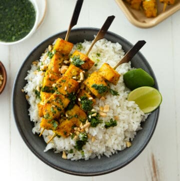 fish skewers on a bed of rice in a black bowl