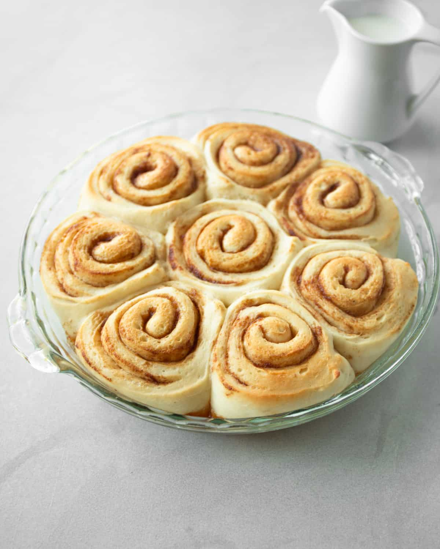 risen cinnamon rolls in a clear baking dish