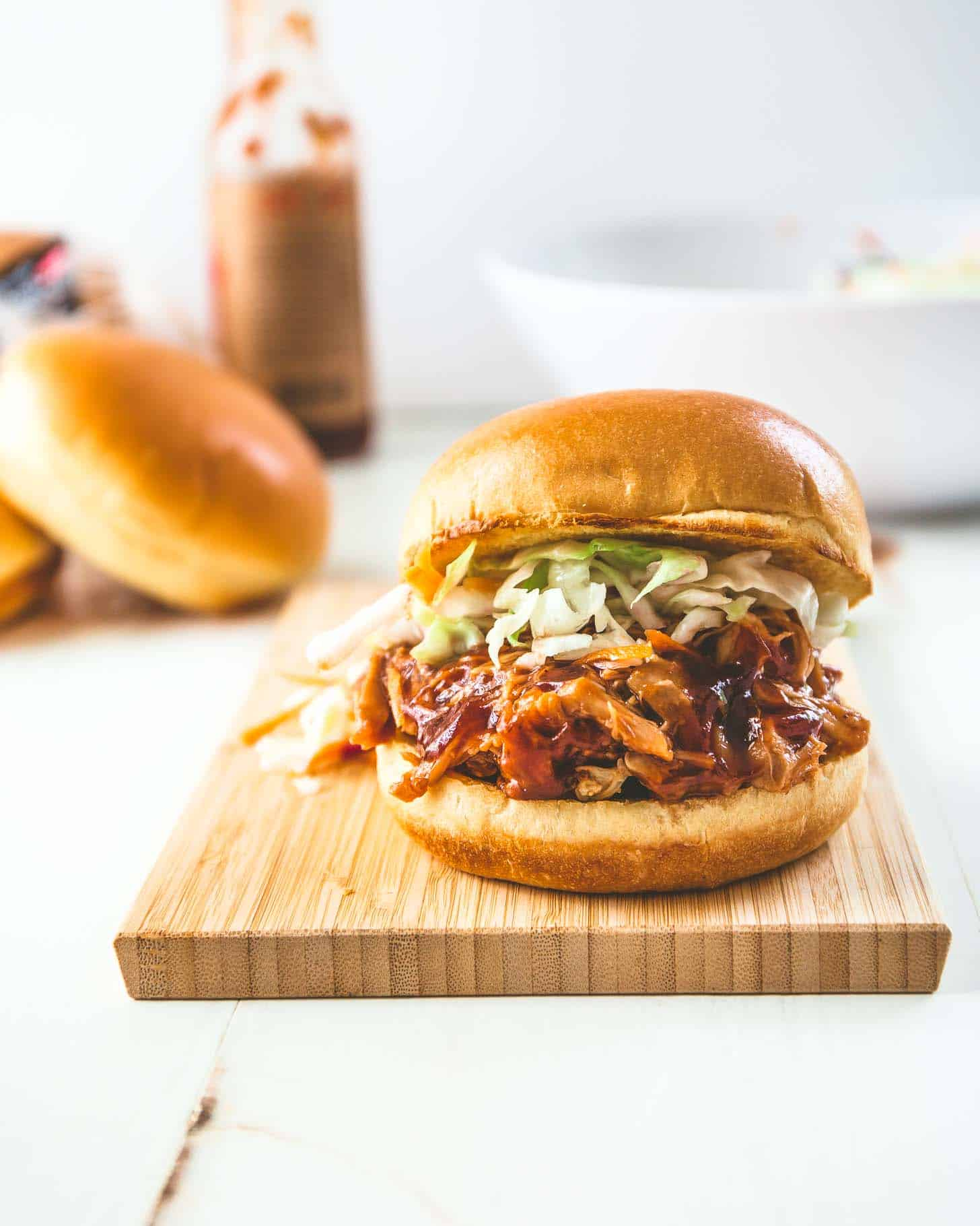 bbq pulled chicken sandwich on a wooden cutting board