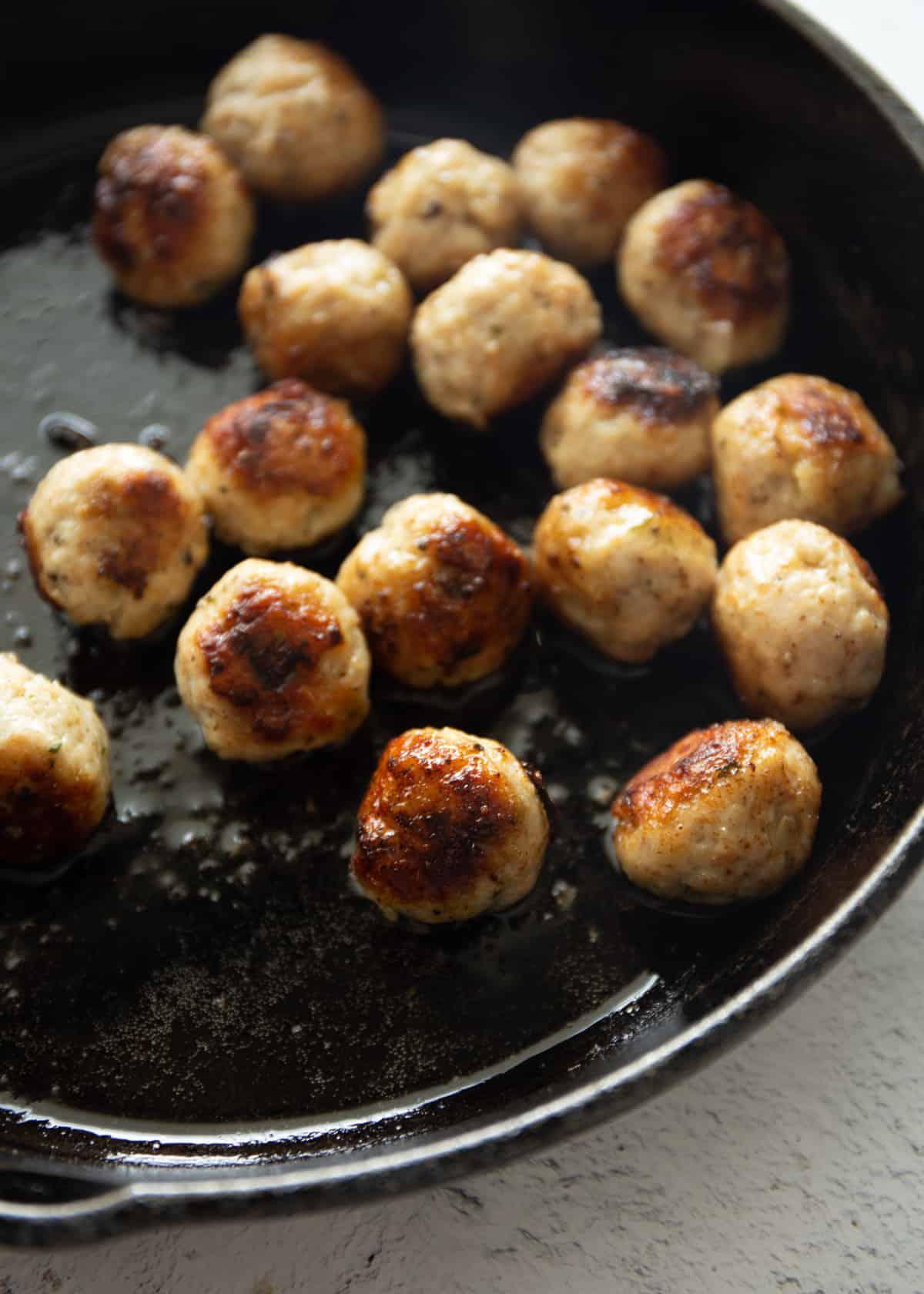 stirring meatballs in a skillet