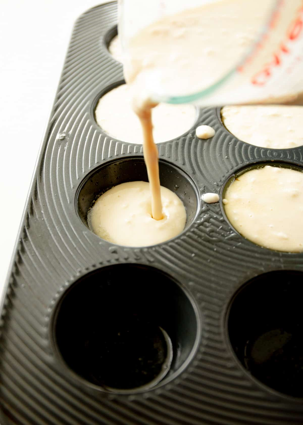 adding batter to a muffin tin