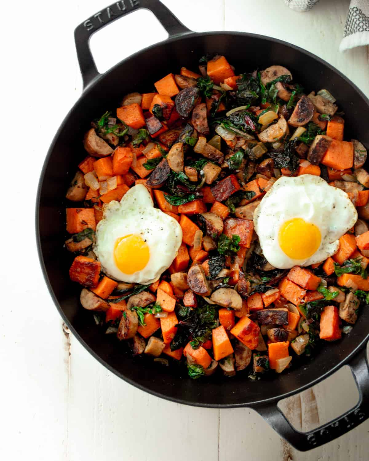 hash in a cast iron skillet topped with fried eggs